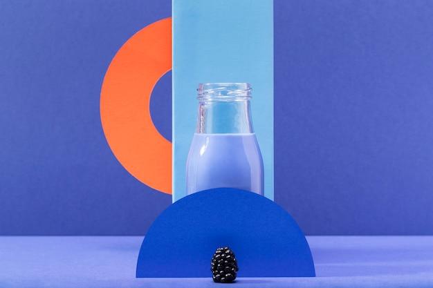 Vista frontal batido azul en botella de vidrio con moras