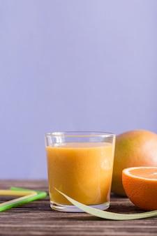 Vista frontal batido de naranja y mango con espacio de copia