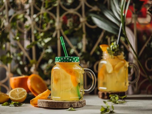 Vista frontal de la bebida de limonada con rodajas de naranja y limón en copa de cóctel con mango y paja sobre un soporte de madera sobre la mesa