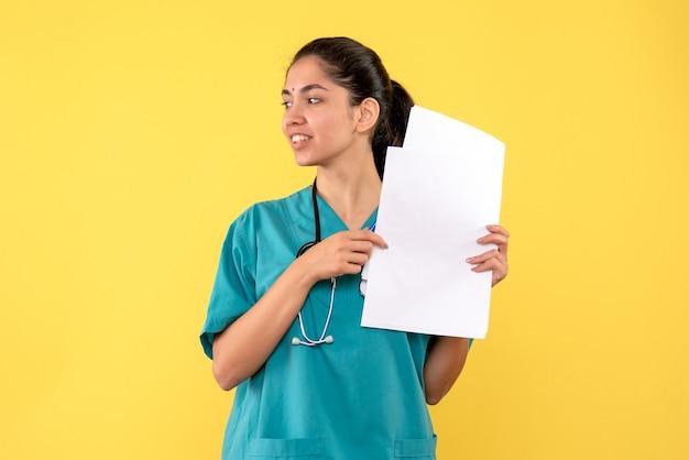 Vista frontal bendita doctora bonita sosteniendo papeles de pie sobre fondo amarillo