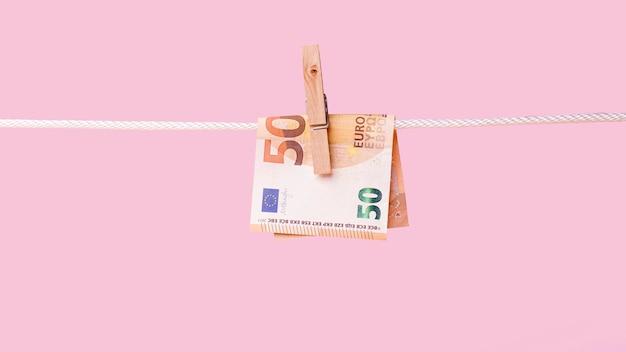 Vista frontal de billetes sostenidos por el pasador de ropa en la cuerda