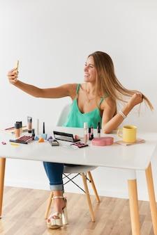 Vista frontal blogger femenina tomando selfies