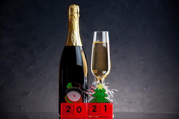 Vista frontal de bloques de madera de botella de vidrio de champán sobre una superficie oscura