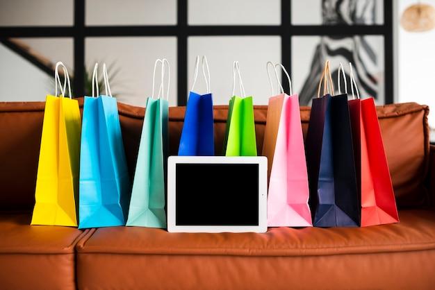 Vista frontal de bolsas de papel de colores y tabletas