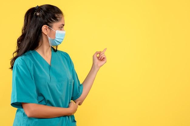 Vista frontal de la bonita doctora con máscara médica apuntando hacia atrás en la pared amarilla