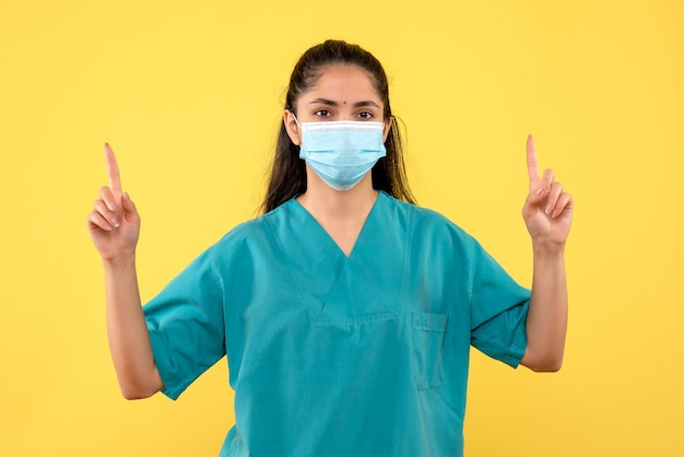 Vista frontal de la bonita doctora con máscara médica apuntando con los dedos hacia arriba en la pared amarilla