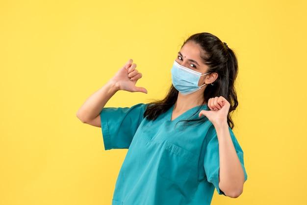 Vista frontal de la bonita doctora con máscara médica apuntando a sí misma en la pared amarilla