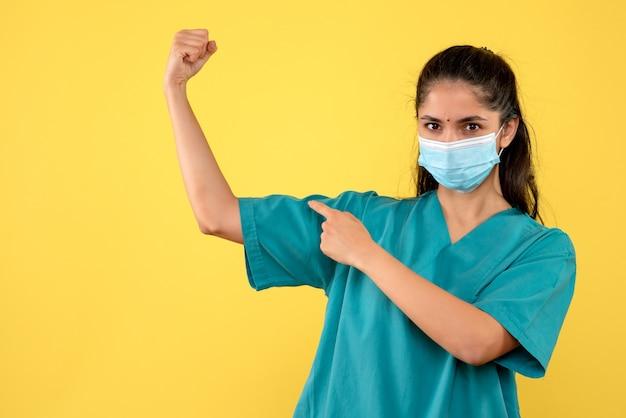 Vista frontal de la bonita doctora con máscara médica apuntando a su músculo del brazo en la pared amarilla