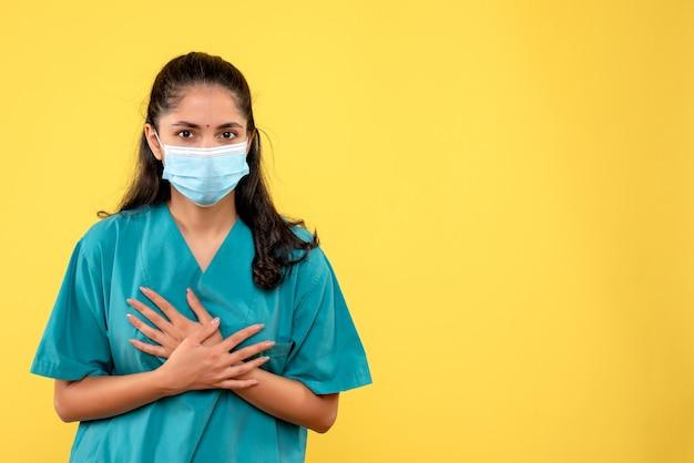 Vista frontal de la bonita doctora con máscara médica poniendo las manos sobre su pecho en la pared amarilla