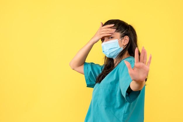 Vista frontal de la bonita doctora con máscara médica sosteniendo su cabeza en la pared amarilla