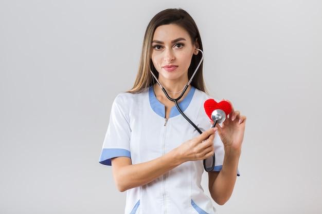Vista frontal bonita doctora sosteniendo un corazón de felpa