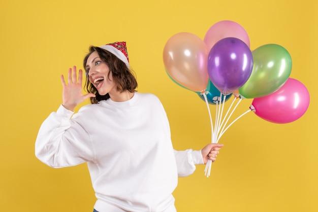 Vista frontal bonita mujer sosteniendo globos de colores en amarillo