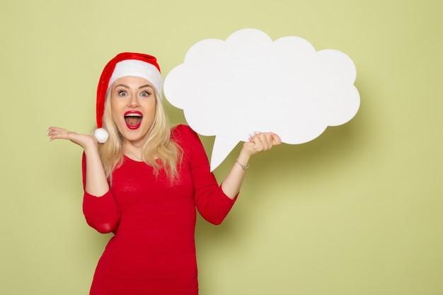 Vista frontal bonita mujer sosteniendo gran cartel blanco en la pared verde año nuevo nieve vacaciones foto emoción navideña