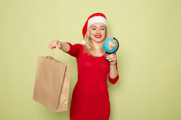 Vista frontal bonita mujer sosteniendo un pequeño globo terráqueo en la pared verde vacaciones emoción navidad año nuevo color