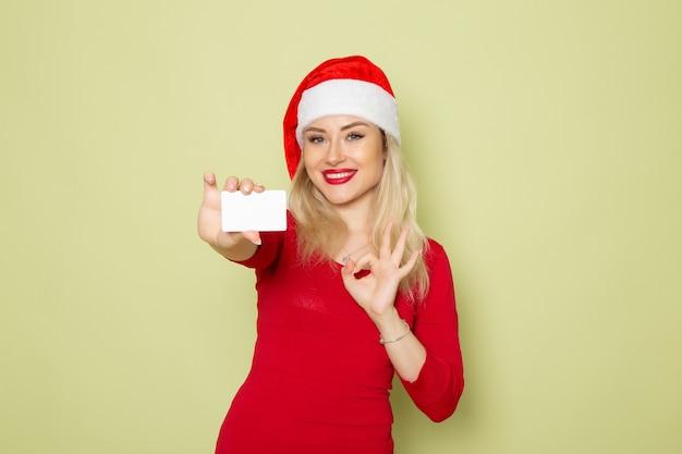 Vista frontal bonita mujer sosteniendo una tarjeta bancaria en la pared verde color navidad año nuevo vacaciones emoción