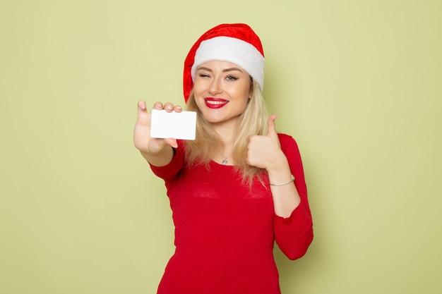 Vista frontal bonita mujer sosteniendo una tarjeta bancaria en la pared verde color navidad nieve año nuevo vacaciones emoción