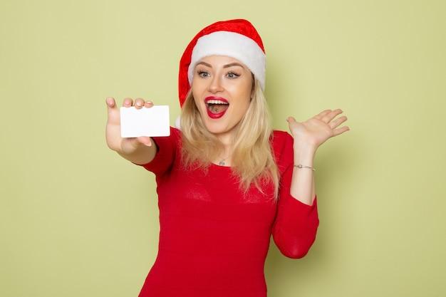 Vista frontal bonita mujer sosteniendo una tarjeta bancaria en la pared verde color navidad nieve año nuevo vacaciones emociones