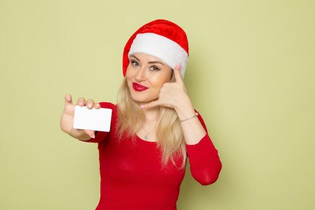Vista frontal bonita mujer sosteniendo la tarjeta bancaria en la pared verde color nieve navidad año nuevo vacaciones emoción