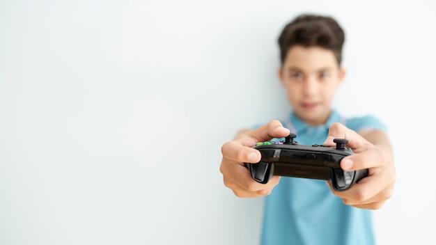 Vista frontal borrosa niño sosteniendo un controlador