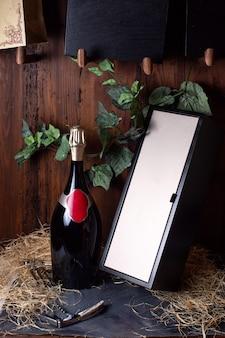 Una vista frontal botella de alcohol botella negra con tapa dorada junto con caja negra y hojas verdes en el fondo marrón beber alcohol bodega
