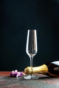 Vista frontal de la botella de champán con copa de vino sobre fondo oscuro