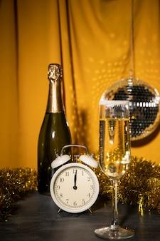 Vista frontal botella de champán y vidrio