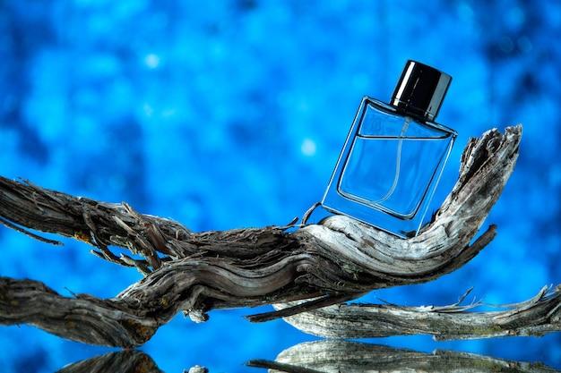 Vista frontal de la botella de colonia de los hombres en la rama de un árbol podrido sobre fondo azul.