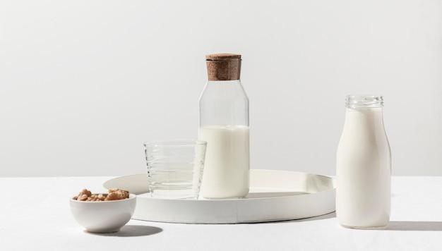 Vista frontal de la botella de leche con nueces en bandeja