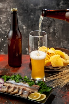 Vista frontal de la botella de oso vertiendo en el vaso con cips y pescado sobre un fondo claro
