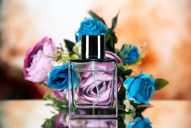 Vista frontal de la botella de perfume de flores de colores sobre fondo borroso beige