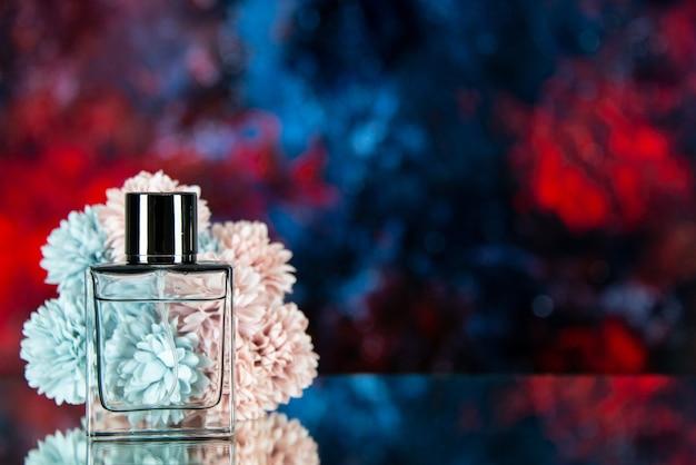 Vista frontal de la botella de perfume flores sobre fondo de acuarela rojo azul oscuro espacio libre