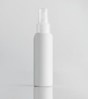 Vista frontal botella de plástico blanco con rociador en una pared blanca