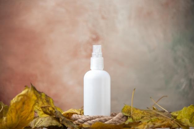 Vista frontal botella de spray vacía alrededor de hojas de otoño sobre fondo desnudo