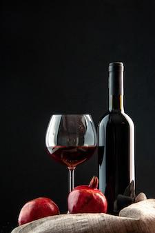 Vista frontal de una botella de vino con una copa de vino sobre fondo negro