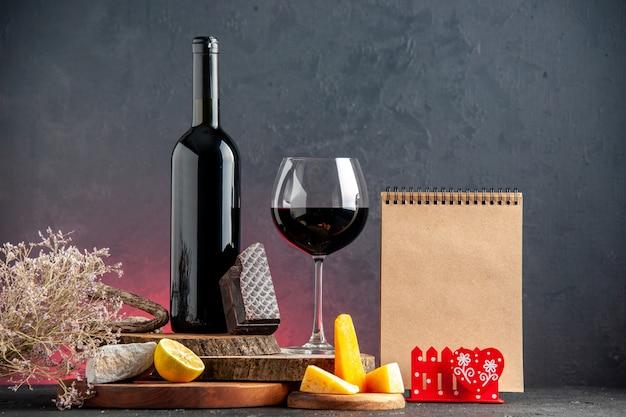 Vista frontal de la botella de vino negro vino en vidrio queso cortado limón un trozo de chocolate negro sobre tablas de madera bloc de notas de rama de flor seca en la mesa roja