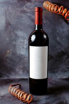 Vista frontal botella de vino tinto negro en el piso brillante