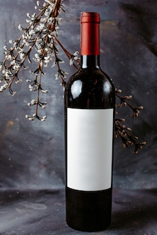 Vista frontal botella de vino tinto en la superficie gris