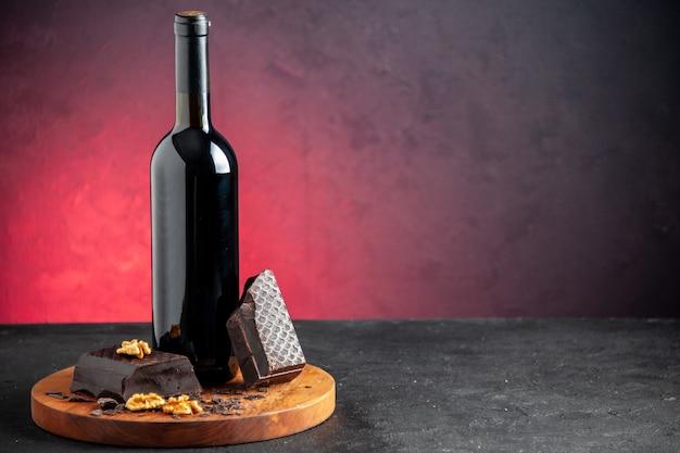 Vista frontal de la botella de vino trozos de nuez de chocolate negro sobre tablero de madera sobre fondo rojo.
