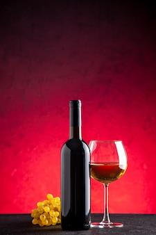 Vista frontal de la botella de vino de uvas amarillas vino en vidrio sobre fondo rojo.