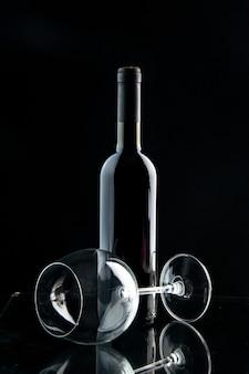 Vista frontal de la botella de vino con vaso vacío sobre un fondo negro