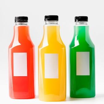 Vista frontal de botellas de jugo multicolores con tapas