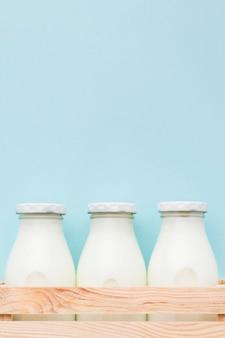Vista frontal botellas de leche fresca con espacio de copia