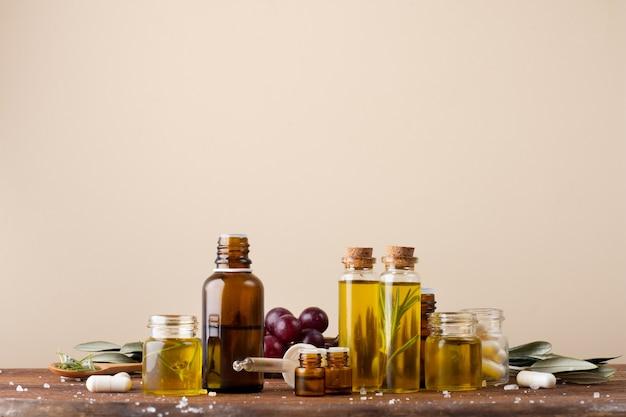 Vista frontal de botellas de plástico con aceite y medicamentos sobre la mesa