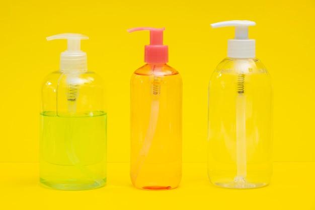 Vista frontal de botellas de plástico con desinfectante para manos y jabón líquido.