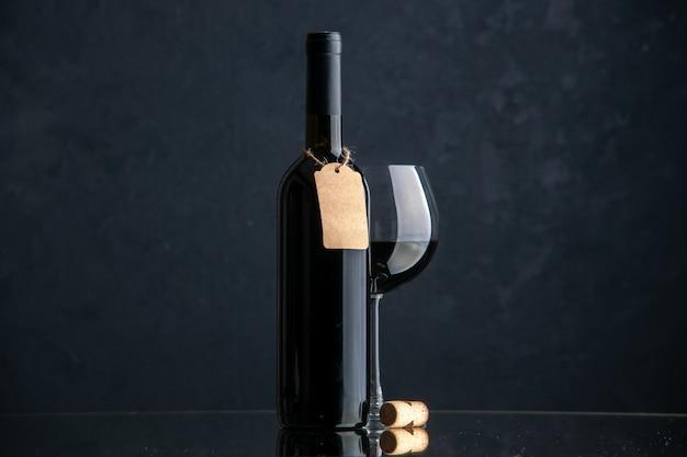 Vista frontal de botellas de vino con copa de vino en la superficie oscura