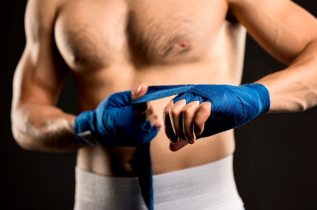 Vista frontal del boxeador masculino poniéndose protección para las manos