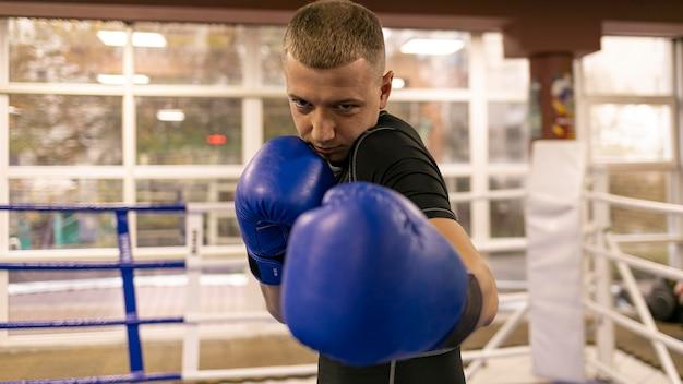 Vista frontal del boxeador masculino practicando con guantes
