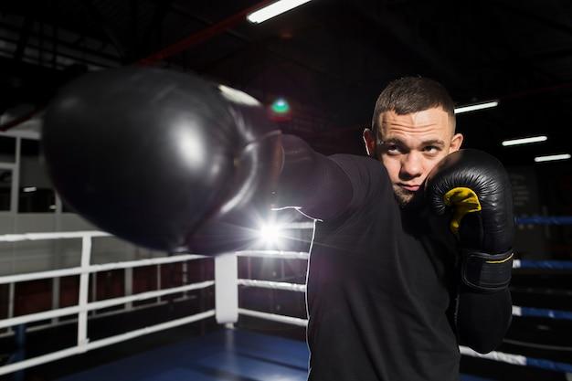 Vista frontal del boxeador practicando con guantes protectores
