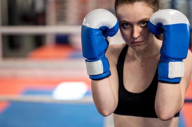 Vista frontal de la boxeadora con guantes protectores y espacio de copia