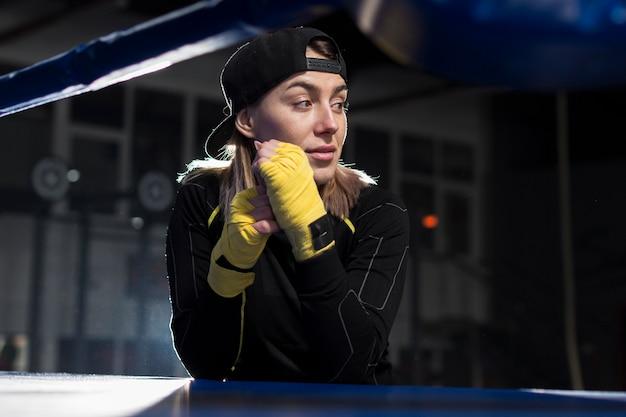 Vista frontal de la boxeadora con guantes protectores posando mientras mira lejos